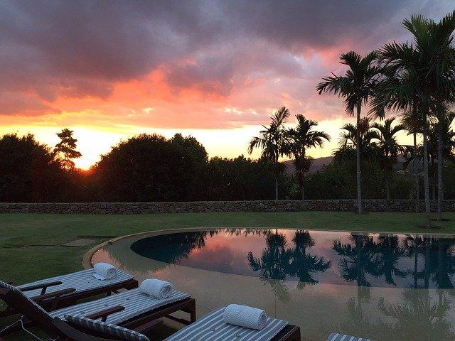 bazén, palmy, lehátka, západ slunce