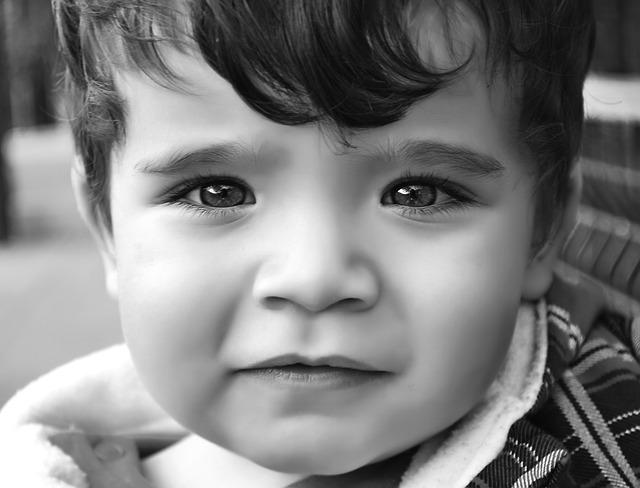Černobílá fotka obličeje usmívajícího se chlapce